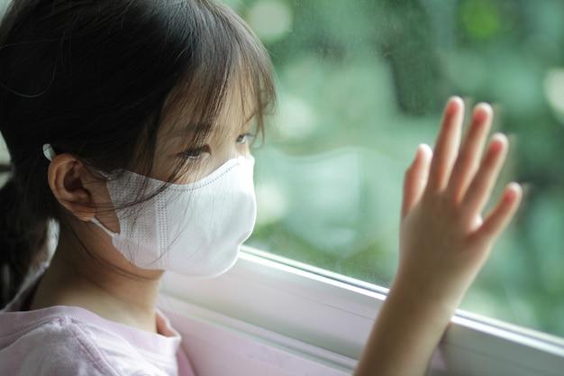 Aziatische jongen van 6 of 7 jaar oud die een medisch masker draagt. klein meisje dat bij het raam staat en naar buiten kijkt. ze ziet er verdrietig en verveeld uit. ze kan ziek zijn of in quarantaine gaan vanwege de coronavirusziekte 19 (covid-19).