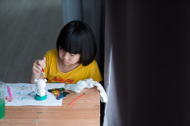 Aziatische jongen verf kleur op papier, onderwijs concept