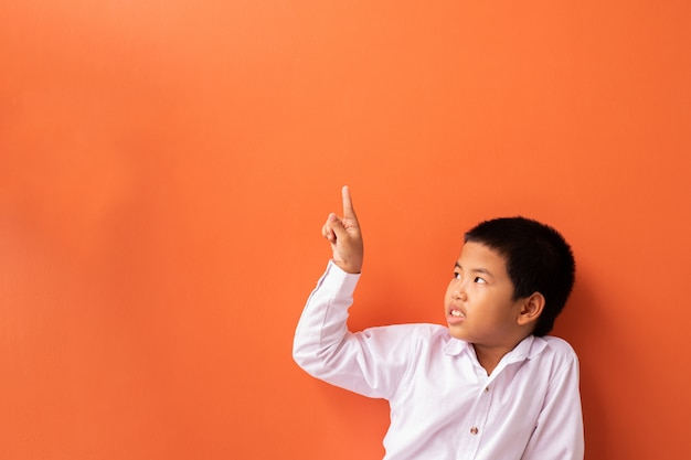 Aziatische jongen wijzende vinger en denken.