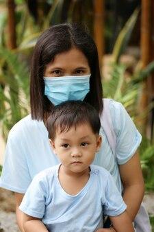 Aziatische jongen zit op moederschoot en moeder draagt groen masker, virusbeschermingsconcept in familie en mensen in de buurt.