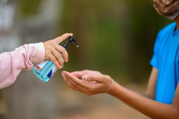 Aziatische jongens dragen hygiënische maskers en gebruiken handdesinfecterend middel als bescherming tegen virussen.