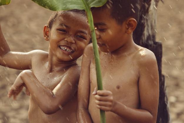 Aziatische jongens zijn blij omdat ze in de regen spelen. na een lange droogte