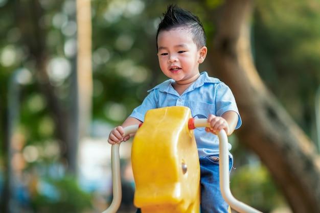 Aziatische jongensglimlach en spel in speelplaats