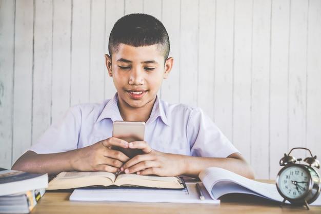 Aziatische jongensstudent die mobiele telefoon spelen op school