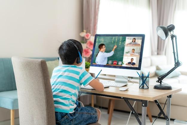 Aziatische jongensstudent videoconferentie e-learning met leraar en klasgenoten