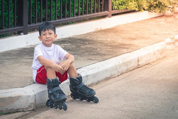 Aziatische jongenszitting die rollerblade schoenen draagt