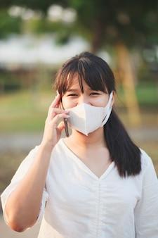 Aziatische jongere vrouw die een beschermingsmasker draagt dat op mobilephone spreekt