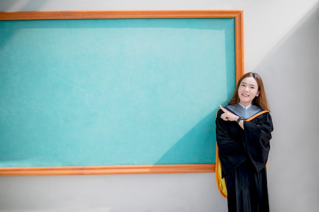 Aziatische jongere vrouw die universitair afstudeerkostuum draagt dat zich voor groen bord bevindt