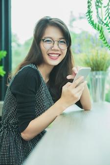 Aziatische jongere vrouw lachen met geluk emotie slimme telefoon lezen