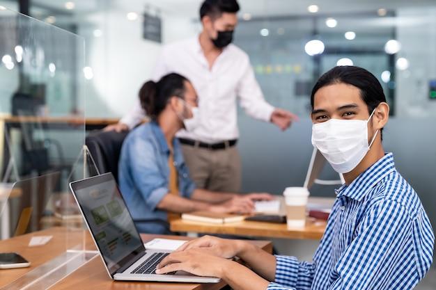 Aziatische kantoormedewerker met beschermend gezichtsmasker werken in nieuw normaal kantoor