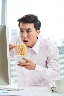Aziatische kantoormedewerker tijdens de lunch