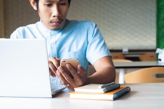 Aziatische kerel die slimme telefoon en laptop computer voor marketing inhoud met behulp van. online marketing.