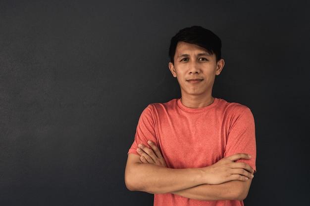 Aziatische kerel in rode lege t-shirt op zwart