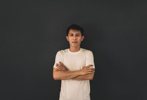 Aziatische kerel in witte lege t-shirt op zwarte muurachtergrond.