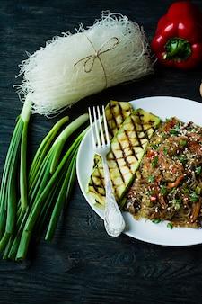 Aziatische keuken. cellofaan noedels versierd met groenten, groenten. funchoza. goede voeding. gezond eten. uitzicht van boven. donkere houten achtergrond.
