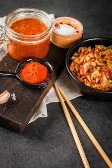 Aziatische keuken. gefermenteerd voedsel. traditioneel koreaans gerecht: kimchi-koolkool met traditionele kimchi-saus van hete rode chili, knoflook, kruiden, zout. zwarte stenen tafel.