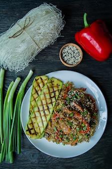 Aziatische keuken. salade van cellofaan noedels, gebakken met groenten, versierd met groenten en krabsticks. funchoza. goede voeding. gezond eten. uitzicht van boven. donkere houten tafel.
