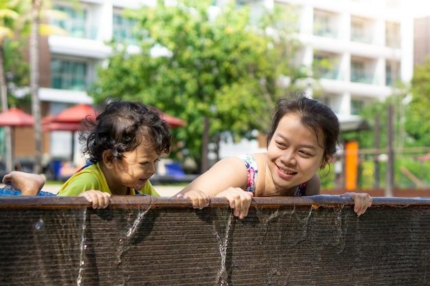 Aziatische kind jongen leren zwemmen in een zwembad met moeder. - zonsondergangfiltereffect