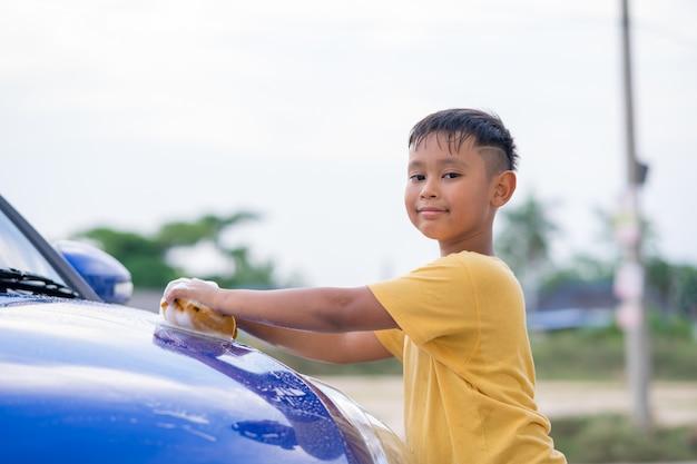 Aziatische kind jongen wassen auto