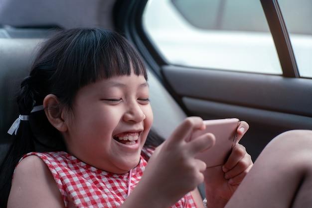 Aziatische kind meisje spelen met smartphone in de auto
