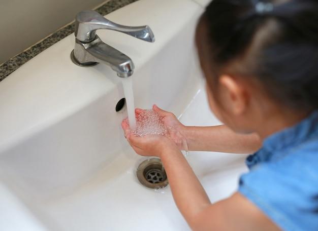 Aziatische kind meisje wassen handen in water putten