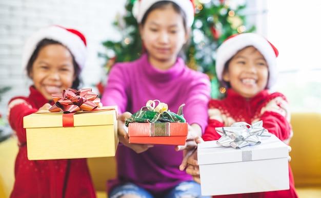 Aziatische kinderen die mooie giftdozen houden en in kerstmisviering geven