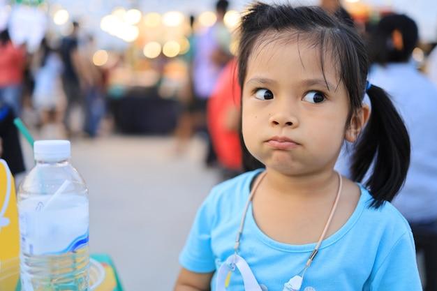 Aziatische kinderen die overdag in het voedselfestival zitten en eten