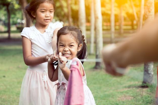 Aziatische kinderen die pret hebben om touwtrekwedstrijd met touw samen in het park in uitstekende kleurentoon te spelen