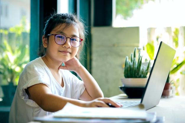 Aziatische kinderen die thuis aan computerlaptop werken
