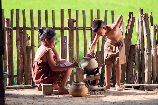 Aziatische kinderen, een jongen en een meisje, koken in de keuken van een thais landhuis, waar ze op het platteland wonen.