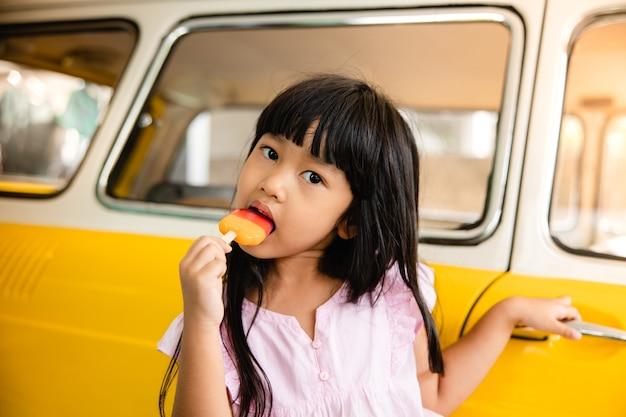 Aziatische kinderen eten van ijs tegen een gele auto in de zomer.