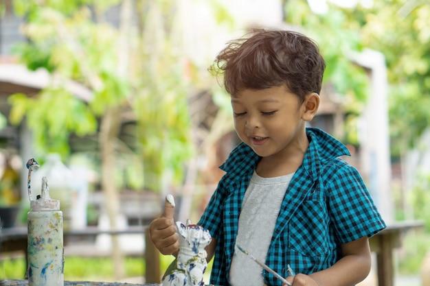 Aziatische kinderen genieten van zijn schilderij met handen