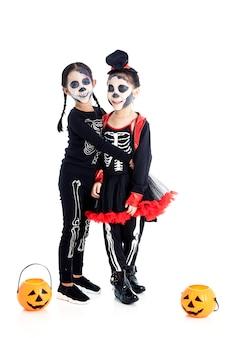 Aziatische kinderen met gezichtsverf en halloween-kostuums