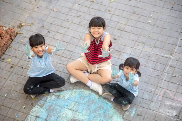Aziatische kinderen spelen buiten. kindmeisje tekent een planeetbol met een kaart van de wereld gekleurd krijt op de stoep, asfalt. aarde, vredesdagconcert.