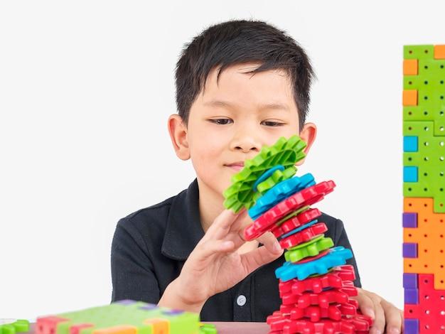 Aziatische kinderen spelen creatief spel met puzzel-plastic blokken