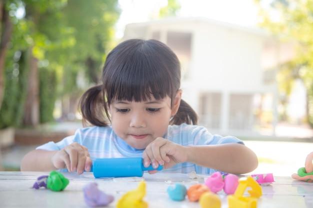 Aziatische kinderen spelen met kleivormen en leren door te spelen