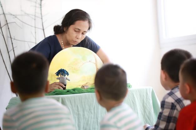 Aziatische kinderen zitten en luisteren naar de leraar die een verhaal vertelt met handgemaakte waldorf-poppen.