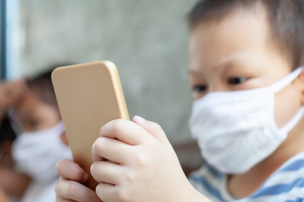 Aziatische kinderenjongen en meisjes die beschermingsmasker dragen die op de smartphone spelen thuis samen quarantaine van het coronavirus covid-19 en luchtvervuiling pm2.5.