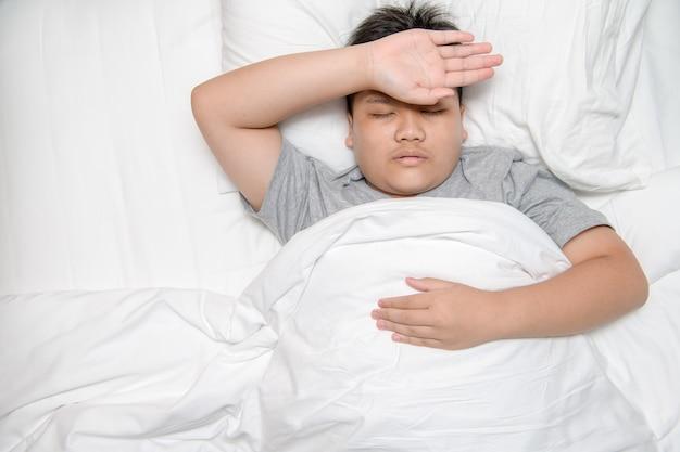 Aziatische kinderziekte die op bed ligt en hand op het voorhoofd legt om de temperatuur te controleren, gezondheidszorgconcept