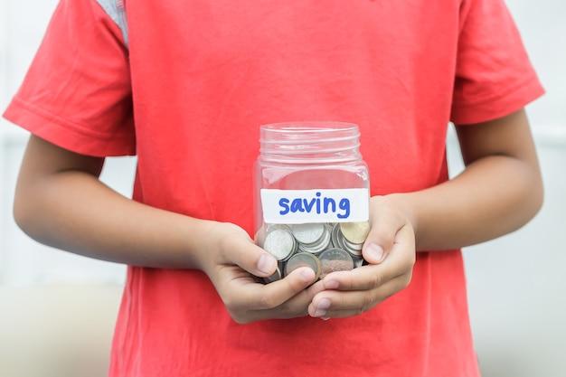 Aziatische kindjongen die de kruik met muntstukken houdt. jeugd met de munten. kid geld besparen voor het toekomstige concept.