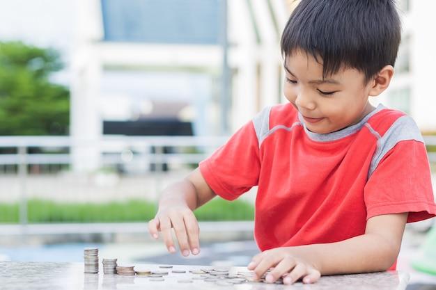 Aziatische kindjongen die de muntstukken telt. de jeugd legde het geld op tafel.