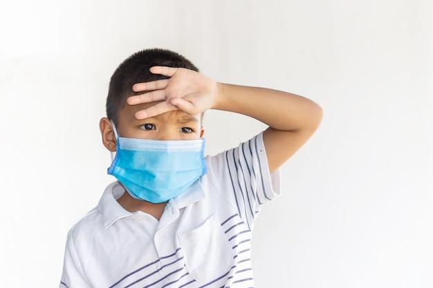 Aziatische kindjongen die een beschermingsmasker draagt om covid-19, corona-virus en pm 2.5-luchtvervuiling te voorkomen. hij heeft een ziekte, keelpijn en griep.