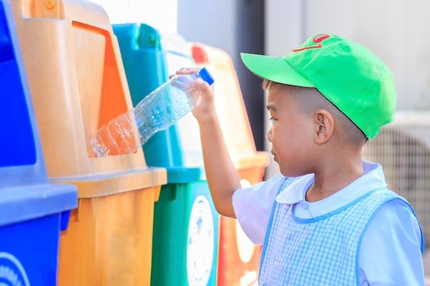 Aziatische kindjongen die een plastic fles in een prullenbak werpt. bewaar het milieuconcept.
