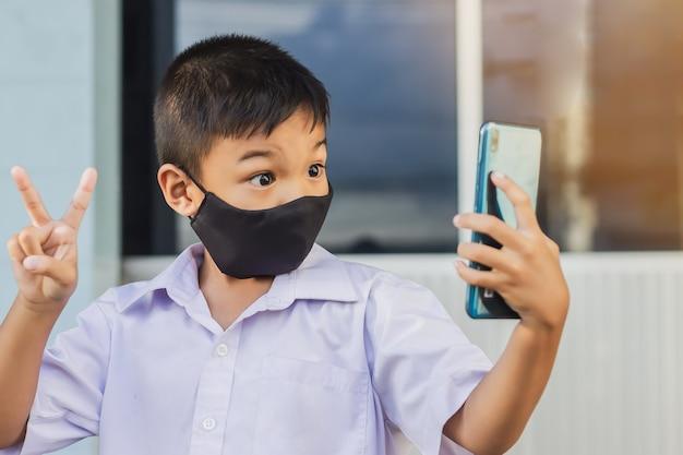 Aziatische kindjongen die een zwart stoffen masker op zijn gezicht draagt ter voorkoming van de ziekte van covid-19 en het coronavirus.