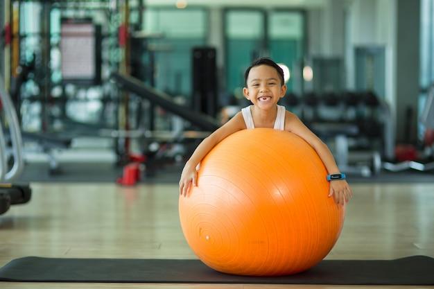 Aziatische kindjongen met gymnastiek- bal