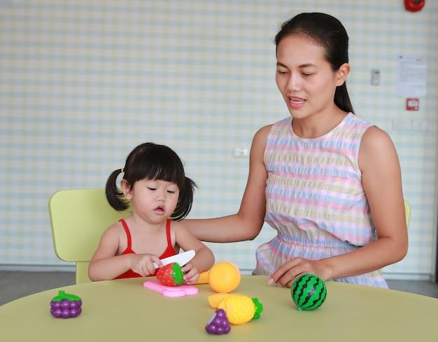 Aziatische kindmeisje en moeder die plastic vruchten spelen bij de jong geitjeruimte