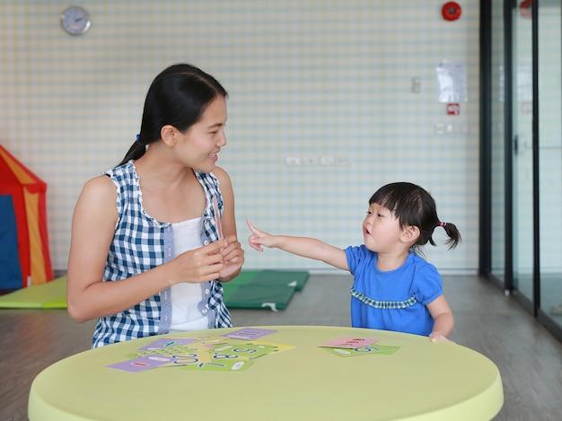 Aziatische kindmeisje en moeders speelflashkaart voor juiste hersenenontwikkeling bij de speelkamer