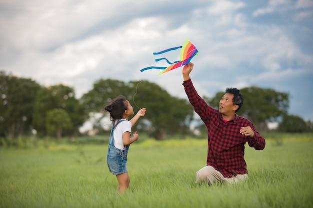 Aziatische kindmeisje en vader met een vlieger die en gelukkig op weide in de zomer in aard lopen