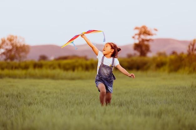 Aziatische kindmeisje en vader met vlieger het lopen