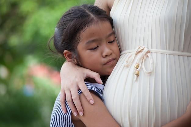Aziatische kindmeisje luisterbaby en het koesteren van de buik van de zwangere moeder met liefde die op nieuw babyzuster wachten